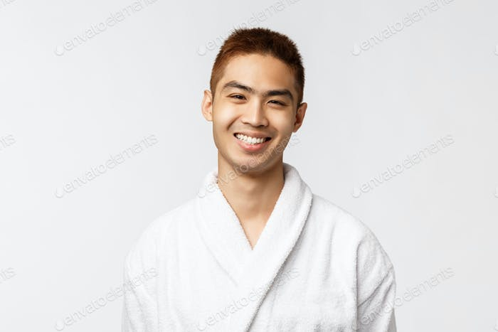 Beauty, spa and leisure concept. Young smiling, cheerful asian man grinning at camera delighted