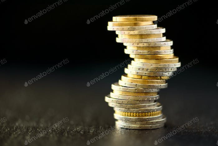 Euro money, currency. Success, wealth and poverty, poorness concept. Euro coins stack on dark black