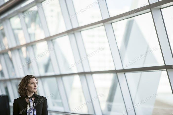 Kaukasische Geschäftsfrau pausiert für einen Moment in der Nähe eines großen Fensters in einer Konferenzzentrums-Lobby.