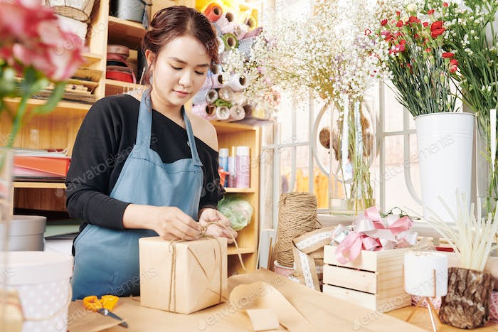 Woman wrapping presents in flower shop