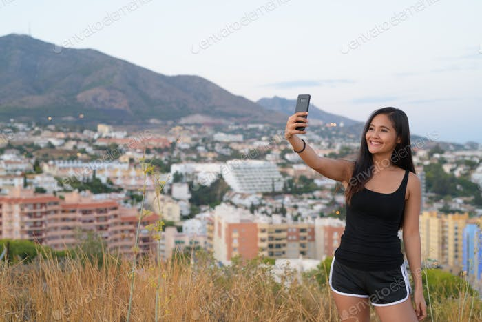 Young Happy Asian Tourist Woman Taking Selfie While Standing On The Hill