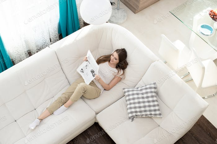 Relaxing girl reading newspaper at home