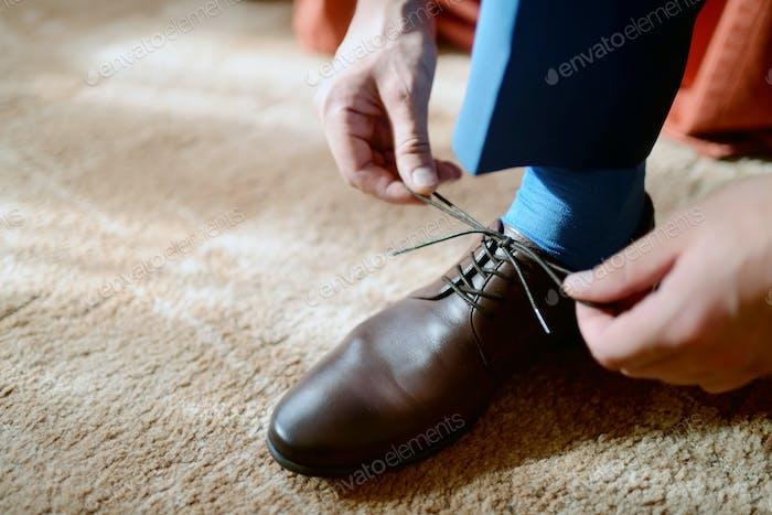 Groom is wearing shoes indoors