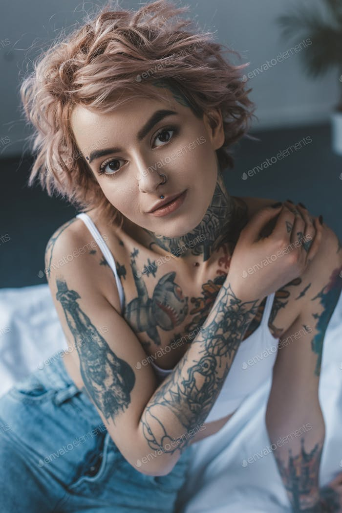 Portrait of Tender Tattooed Girl With Pink Hair in Bedroom