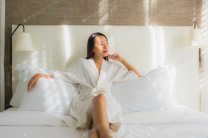 Retrato hermosa joven asiático mujer relajarse sonrisa en cama en dormitorio