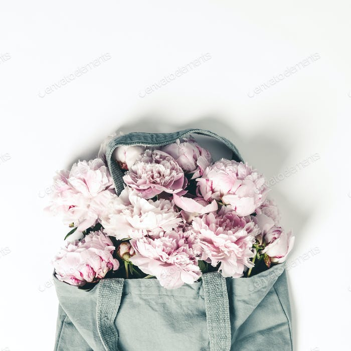 Blue cotton eco tote bag with peony flowers on white background, flat lay