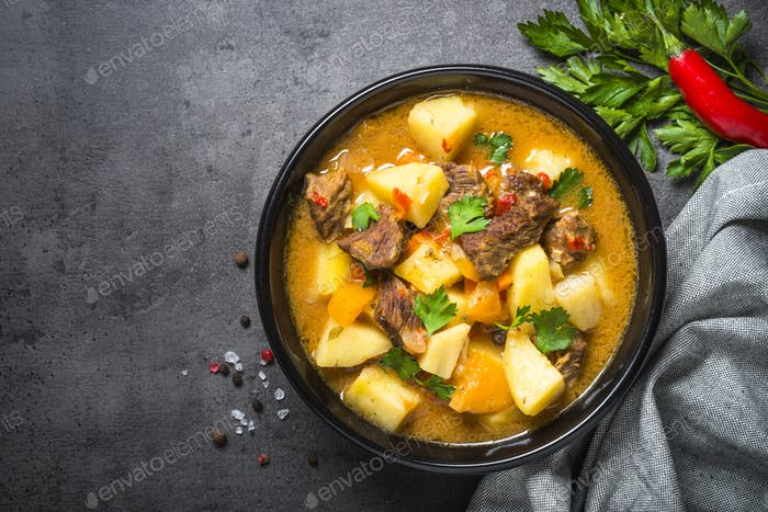 Beef stew with vegetables - carrot, ppototo and pumpkin on black