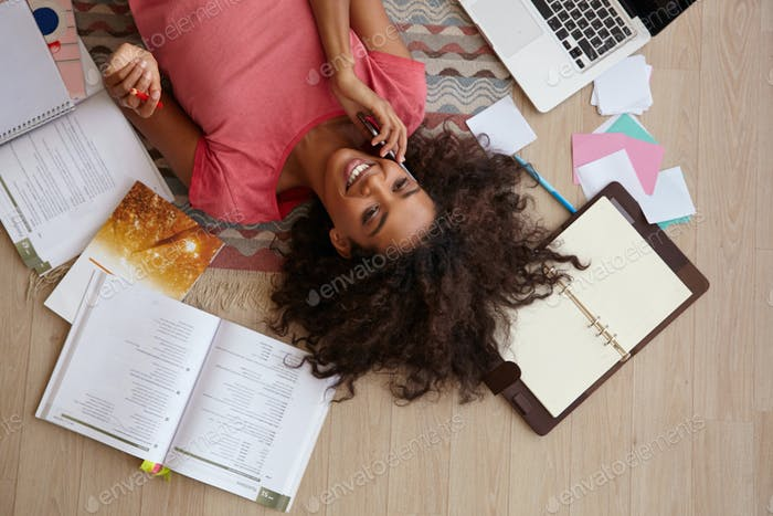 Indoor top view of beautiful young curly female with dark skin, making break with homework