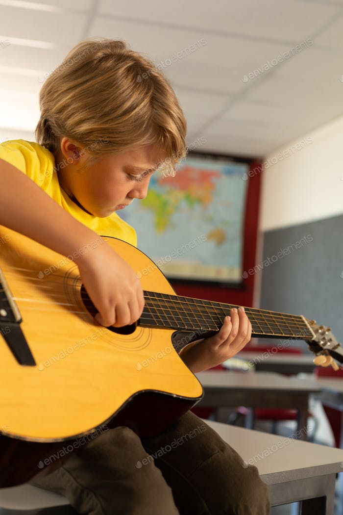 Side view of Caucasian boy playing guitar in a classroom at elementary school