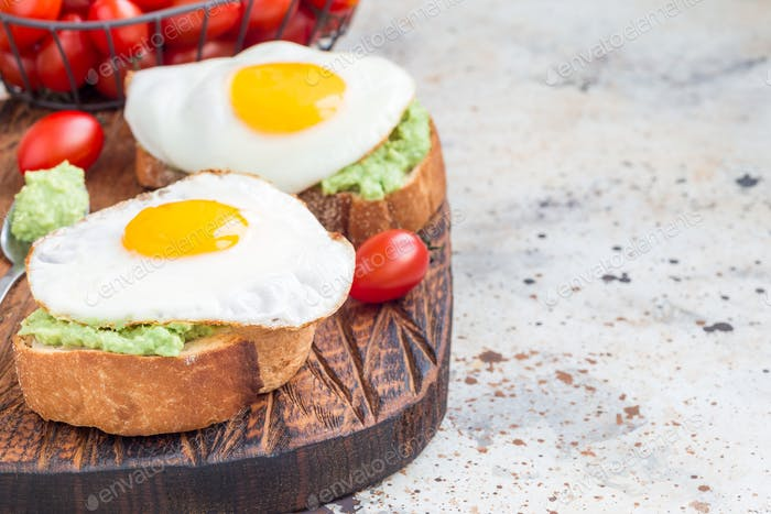 Open sandwiches with mashed avocado and fried egg on a toasted bread, horizontal, copy space