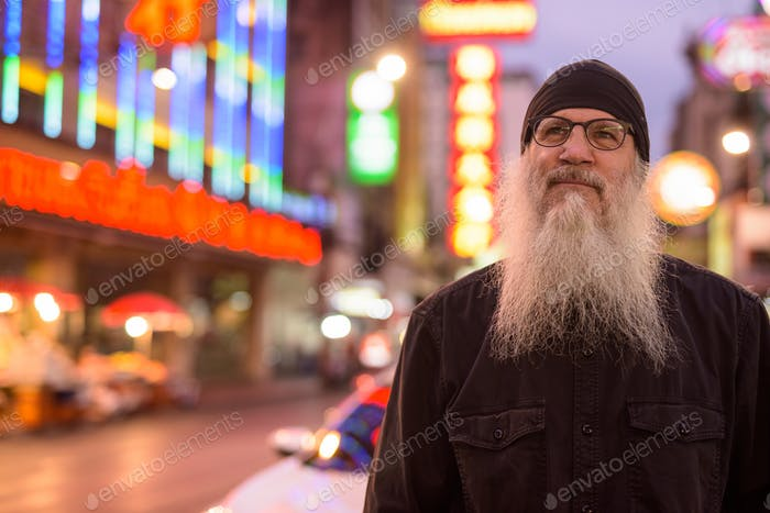 Face of mature bearded tourist man with eyeglasses thinking in Chinatown at night
