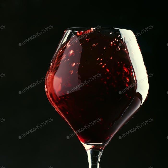 Rotwein, Spritzer im Glas, trockener Cabernet Sauvignon, dunkler Hintergrund
