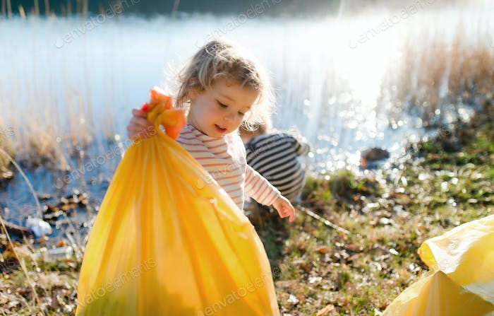 Small children collecting rubbish outdoors in nature, plogging concept