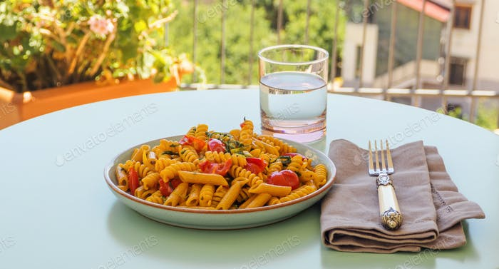Whole grain pasta dish with tomatoes and rocket