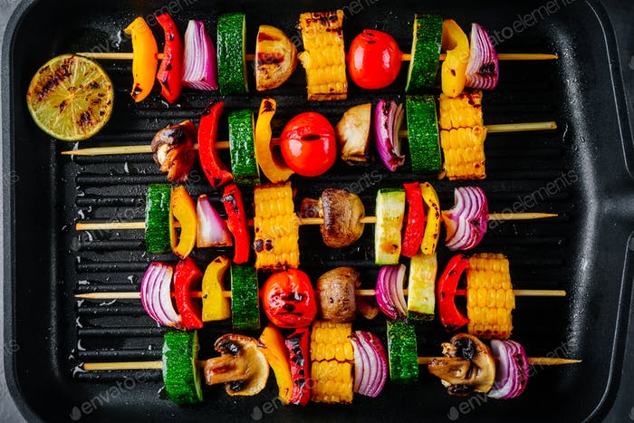 Grilled vegetable skewers with sweet corn, paprika, zucchini, onion on a grill pan