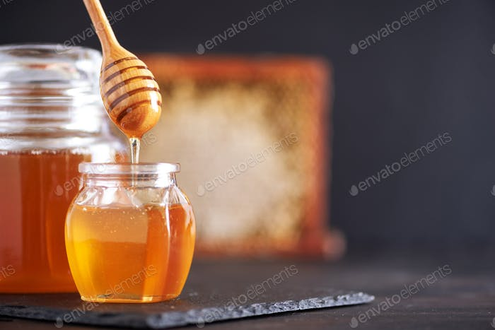 Honey jar, honeycomb and wooden spoon in jar on black background. Copy space. Autumn harvest concept