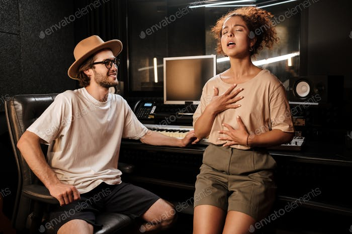 Attractive singer girl intently singing for musical producer in modern studio