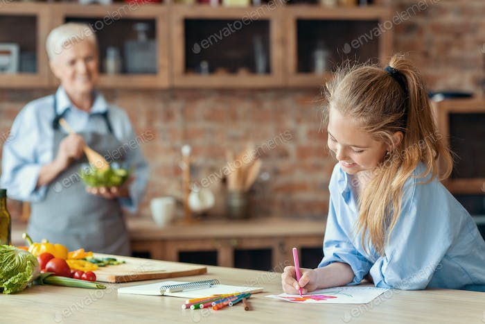 Little girl drawing at kitchen while helping granny