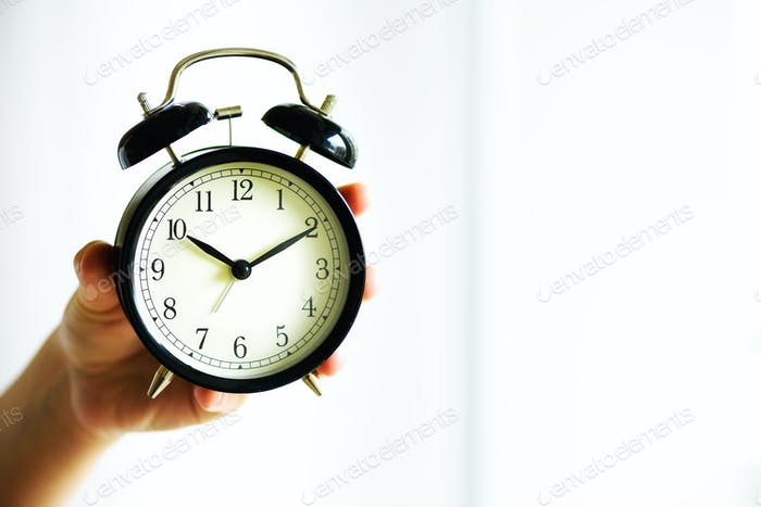 Classic black alarm clock in a hand. Sunny morning light. Copy space