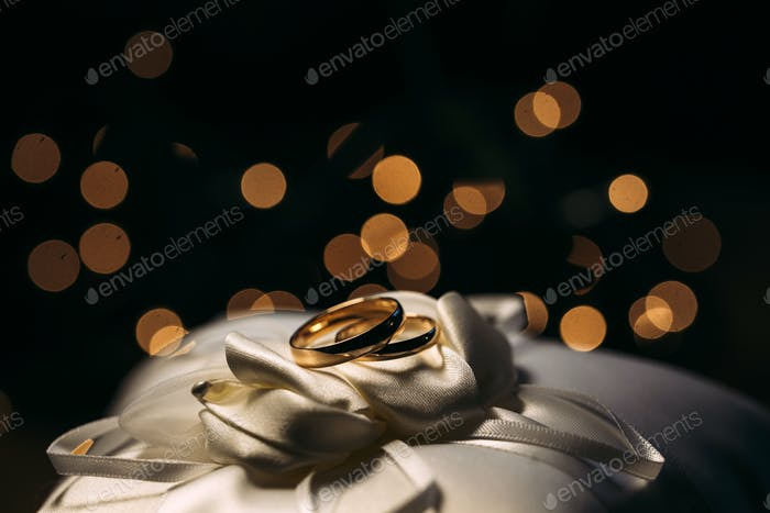 Golden wedding rings on silk cloth with bokeh lights in background