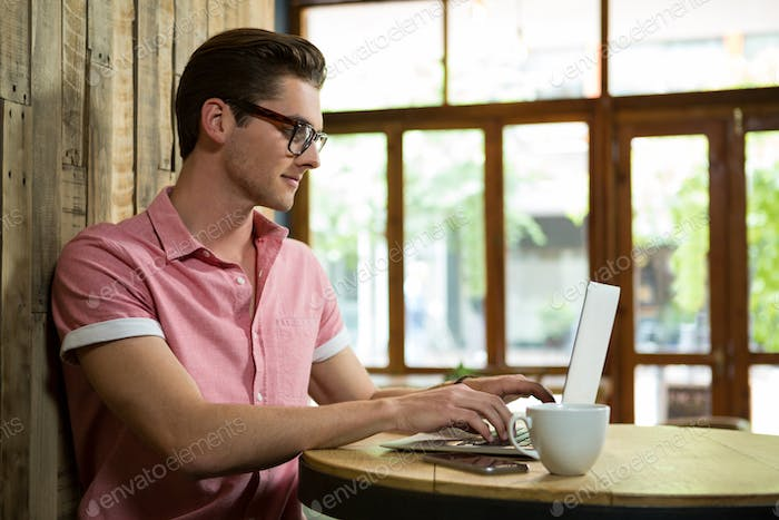 Handsome young man using laptop at table in coffee shop