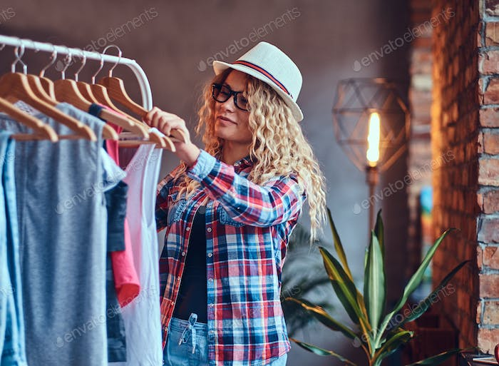 A woman chooses fashionable clothes on the coat rack.