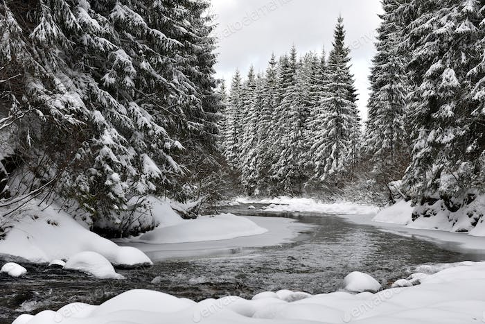 Winter landscape of a small snowy river after blizzard