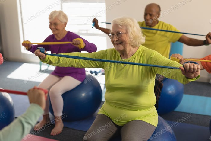 Front view of happy senior people exercising with resistance band in fitness studio
