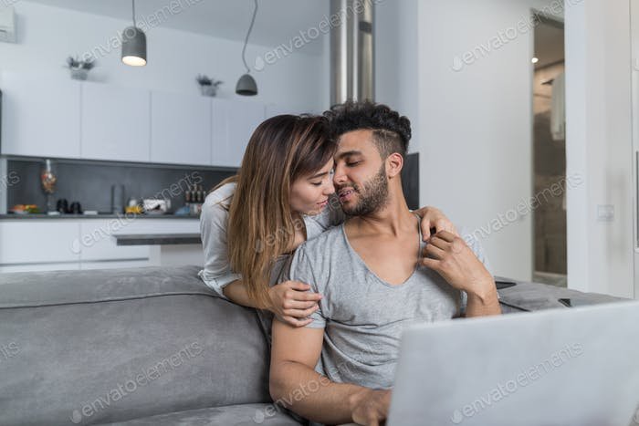 Beautiful Woman Kiss Man Sitting On Couch With Laptop Computer In Modern Apartment Young Couple
