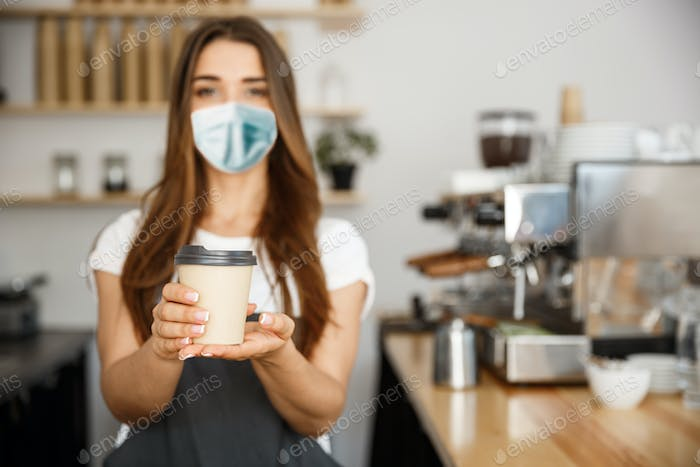 Business Owner Concept - Beautiful Caucasian Barista in face mask offers disposable take away hot
