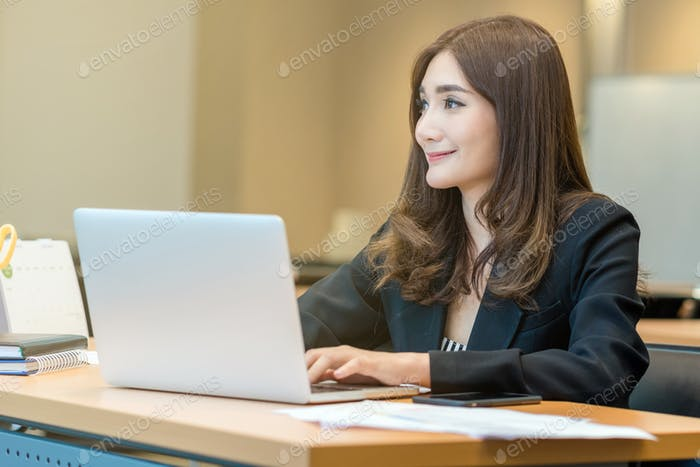 Asian Businesswoman in formal suit working with computer laptop and office supplies in modern office