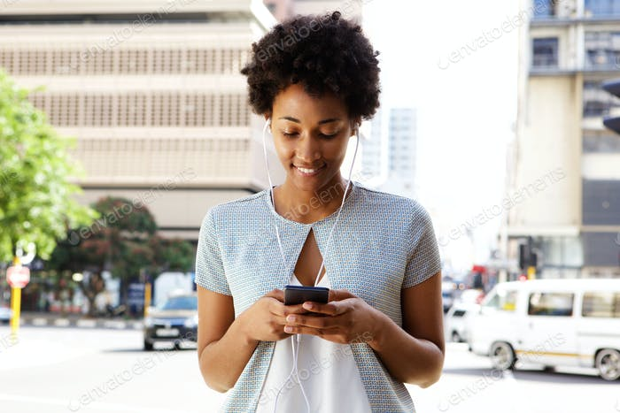 Young black woman listening to music on her cell phone