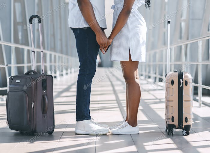 Black millennial couple holding hands at airport, standing with luggage