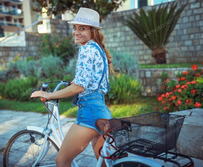 Happy woman riding on bike outdoors