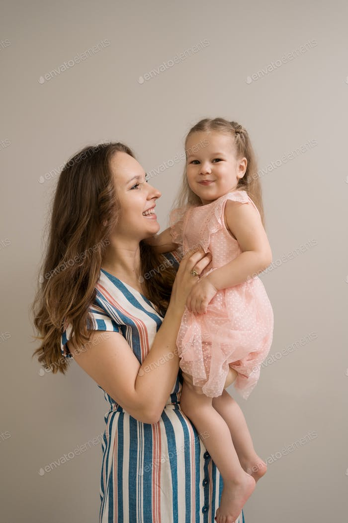 Mother and daughter portrait on beige background