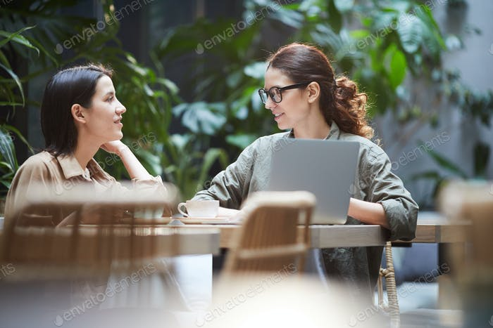 Confident ladies working on web design