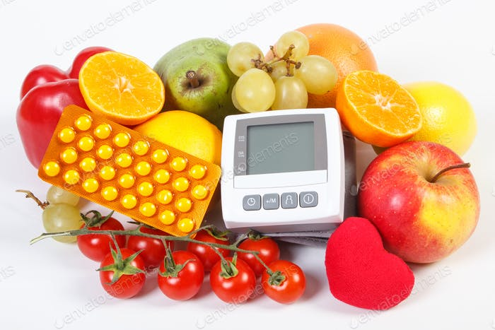 Blood pressure monitor, fruits with vegetables and medical pills