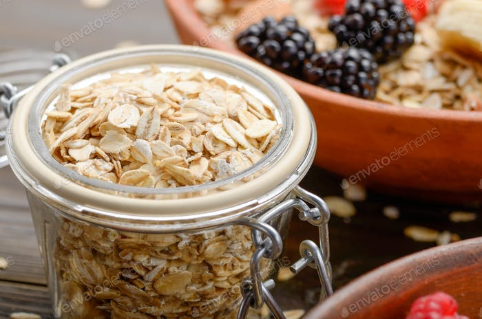 Glass gar with oats with bowl of muesli and berries aside closeu