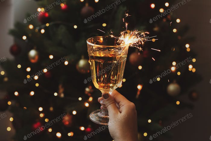Hand holding champagne glass with burning firework at christmas tree in dark room. Happy New Year!