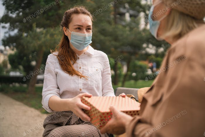 Young woman giving present to grandmother outdoors in city, life after covid-19 vaccination
