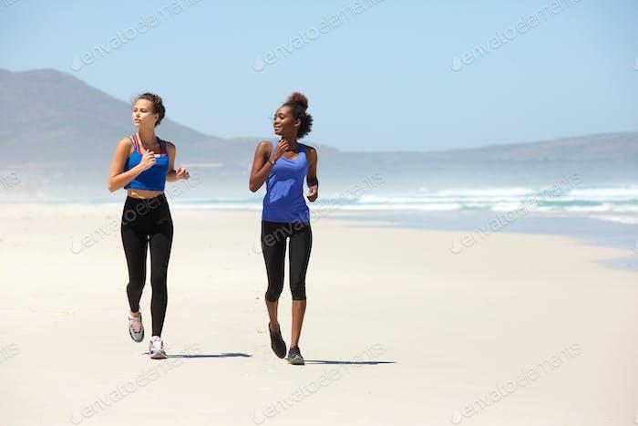 Zwei junge fit Frauen laufen am Strand