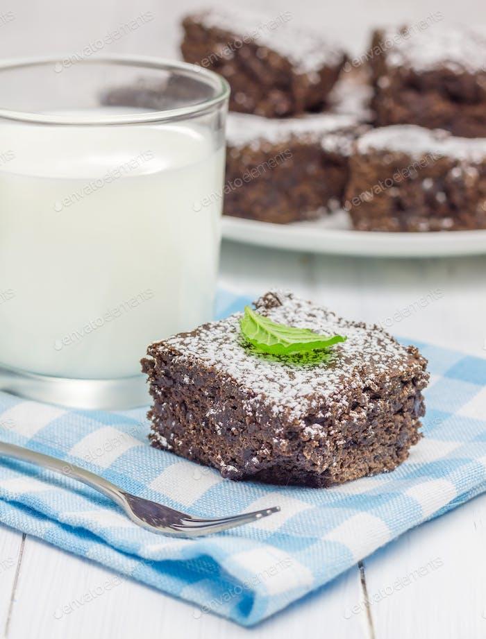 Zucker pulverisierte hausgemachte Brownies mit Glas Milch
