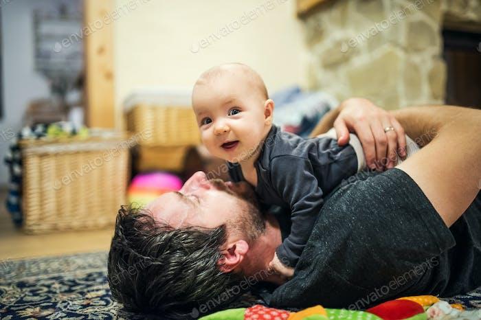 Vater liegend auf dem Boden mit einem kleinen Mädchen zu Hause.