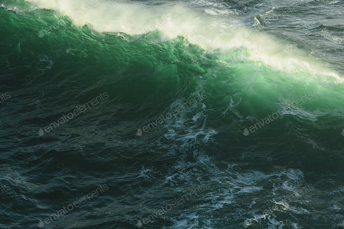 Detail of crashing waves, surf and crest, windblown mist curling from the white water, and deep