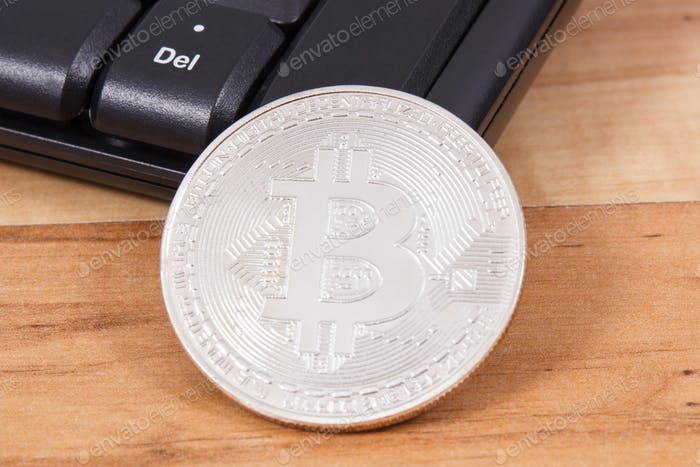 Silver bitcoin and computer keyboard as symbol of mining cryptocurrency