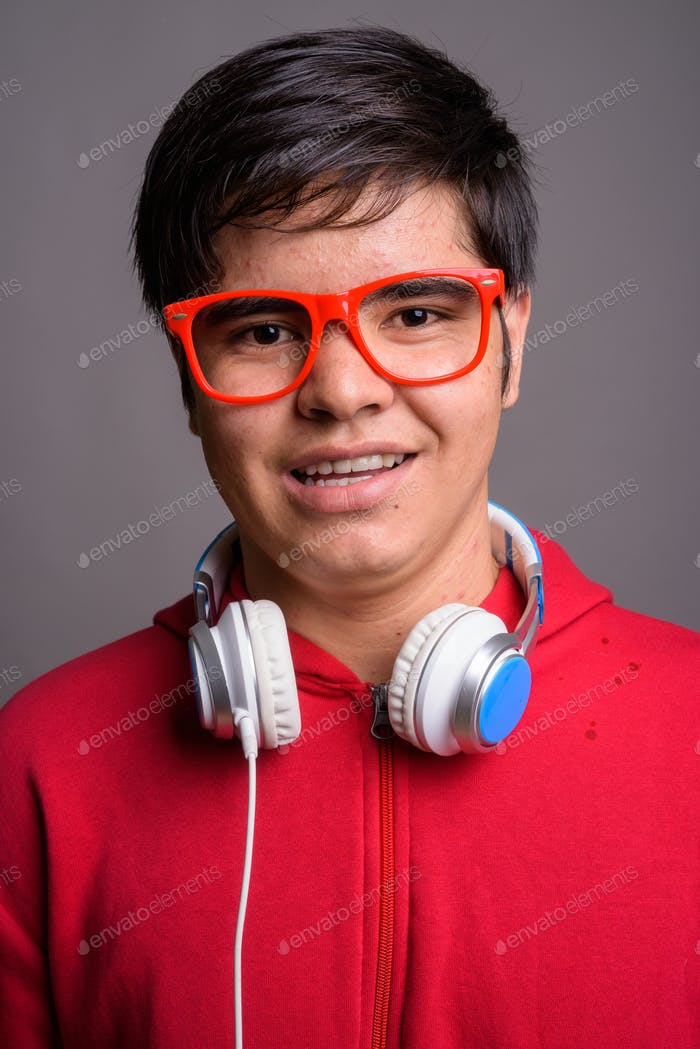 Young Asian teenage boy wearing headphones against gray backgrou