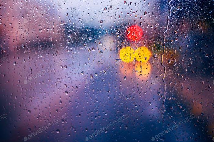 Water Drops Of Rain On Blue Glass Background. Street  Bokeh Ligh