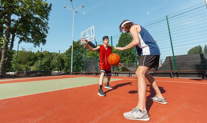 Panoramic view of two professional basketball players training for competition at outdoor court