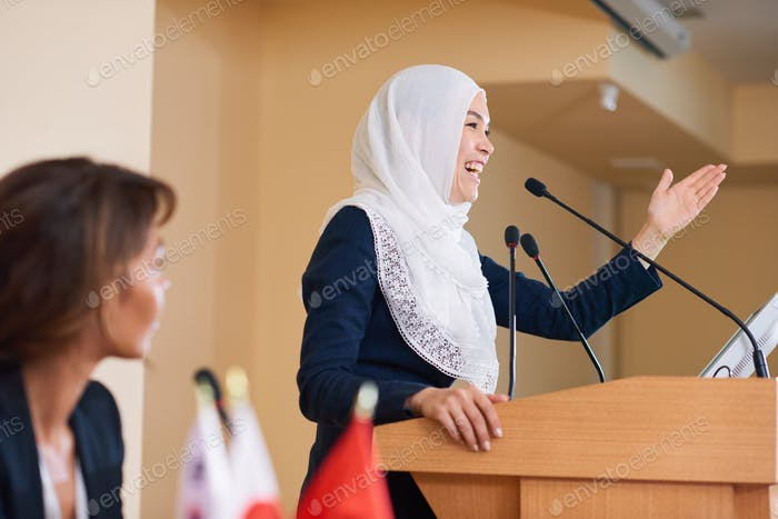 Happy young female speaker in hijab laughing while standing by tribune