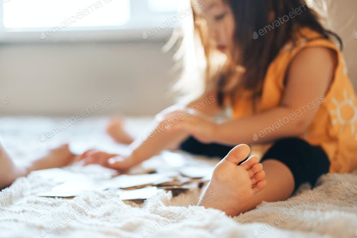 The child plays educational games in the room on the bed